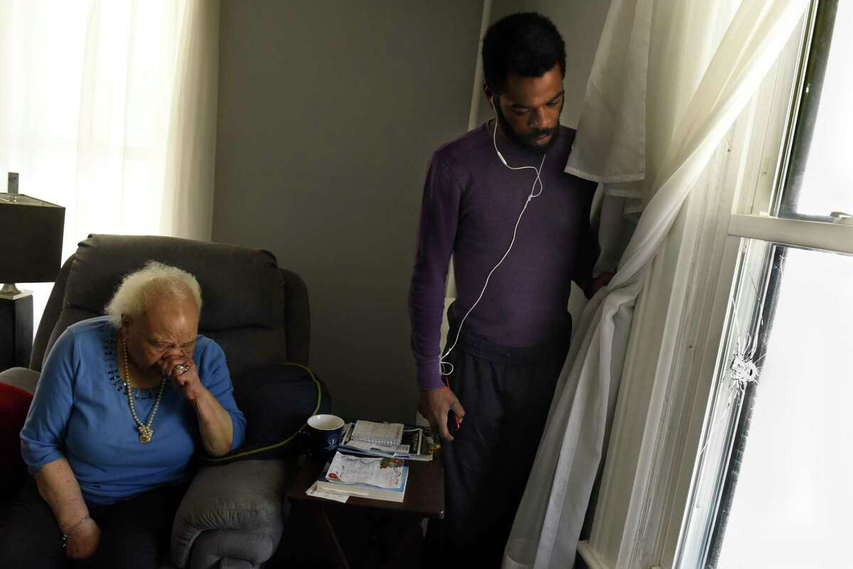 Ann Farmer and her grandson Omar McGill are seen next to a window with a bullet hole on Wednesday, May 20, 2020 in Schenectady, N.Y. A man died  in a late-night shooting Tuesday on Victory Avenue. Ann Farmer lives in the house with her daughter, who was lying on her couch when she heard shooting. A bullet came in one of her windows and exited through another window of the house.  (Lori Van Buren/Times Union)