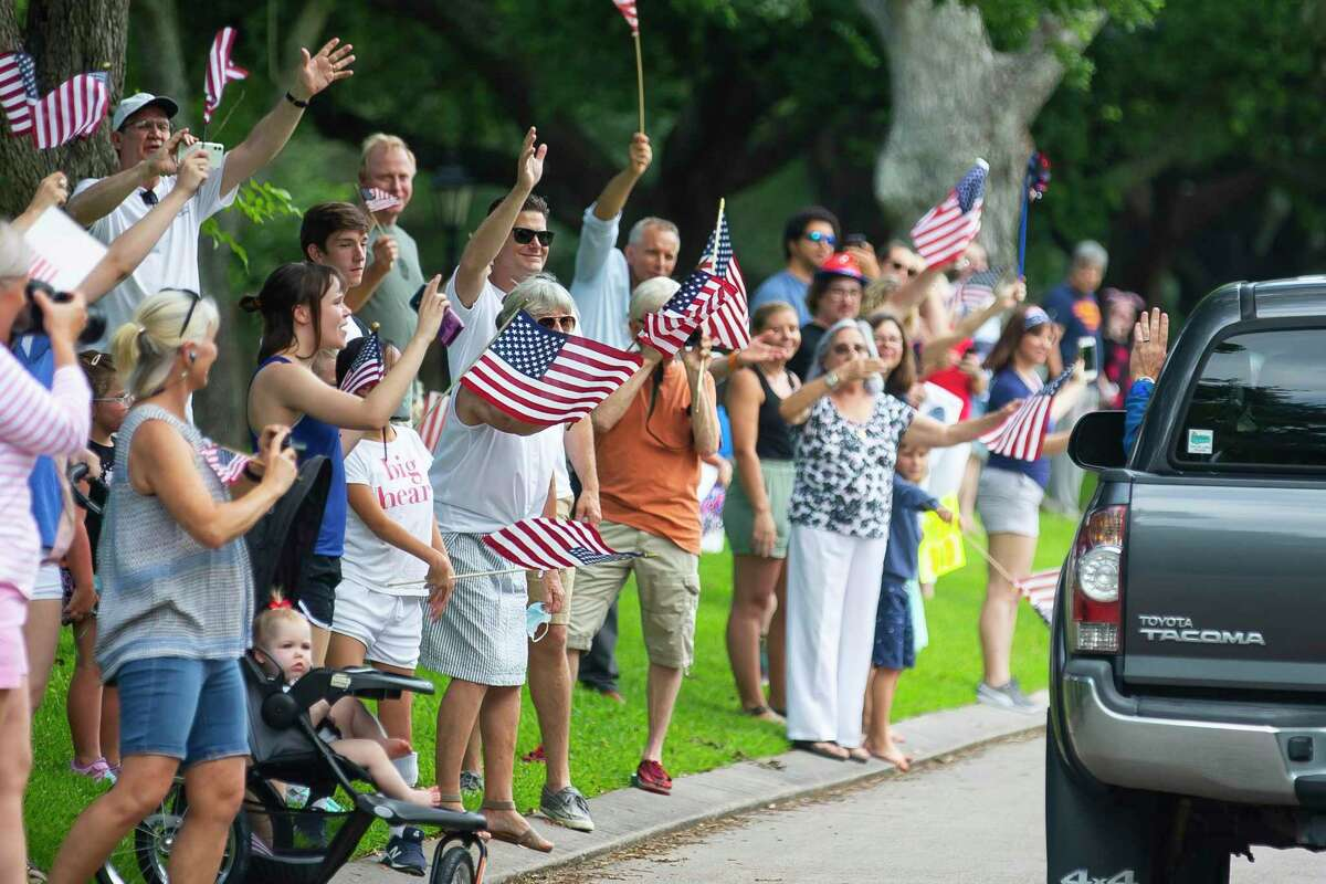Neighbors in the Timber Cove subdivision wave farewell to Astronaut Bob Behnken as he departs his Houston neighborhood for Florida for the upcoming launch of the SpaceX Falcon 9 rocket and Crew Dragon spacecraft, Wednesday, May 20, 2020, in Seabrook.