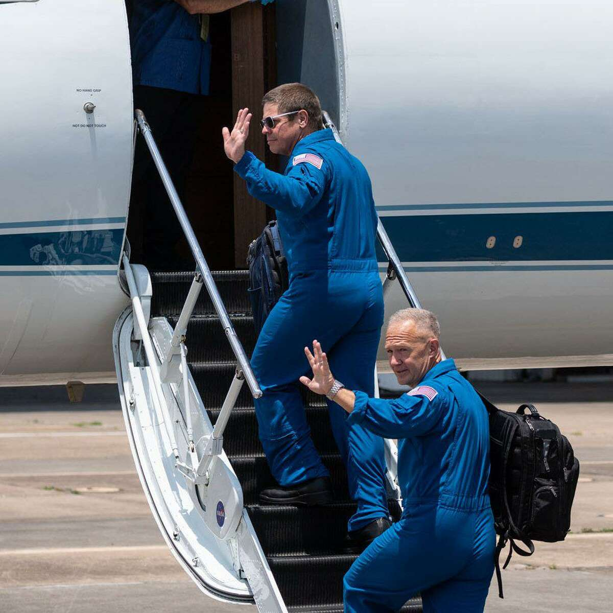 Astronauts Bob Behnken, top, andDoug Hurley board a planeat Ellington Airport on May 20, 2020. They are departing Houston for Kennedy Space Center in Florida, where they will launch into space on May 27 on a SpaceX Falcon 9 rocket and Crew Dragon spacecraft.