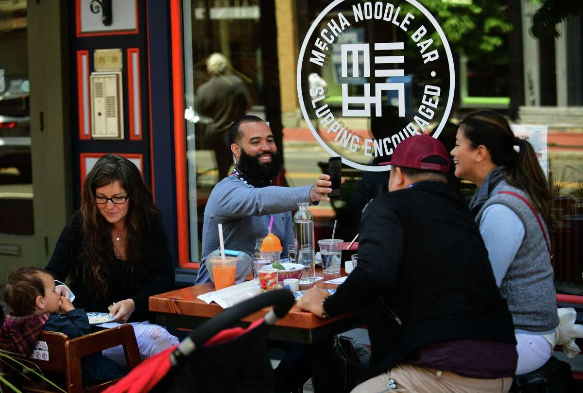 Local residents get out to enjoy the town Wednesday , including patrons at Mecha Noodle Bar on Washington Street in Norwalk during the limited reopening after the quarantine due to the coronavirus outbreak.
