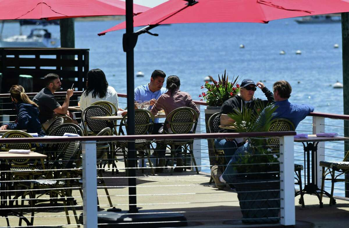 Local residents get out to enjoy the town Wednesday May 20, 2020, including patrons of Harbor Lights restaurant during the limited reopeneing after the quarantine due to the coronavirus outbreak in Norwalk, Conn. Salons were asked not to reopen until June.