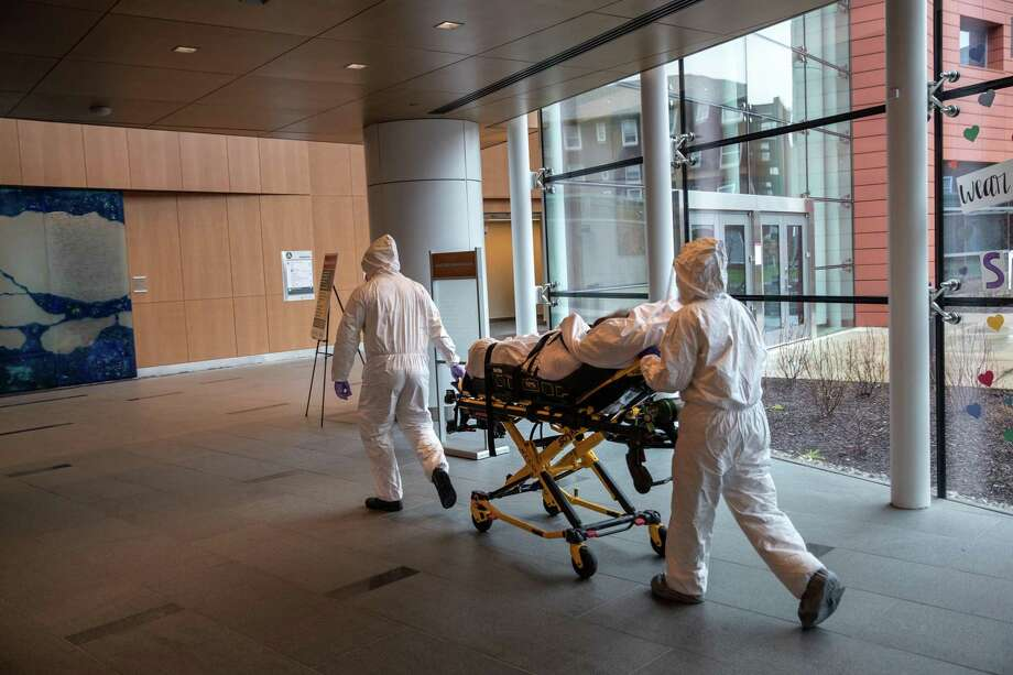 Medical staff transported a COVID-19 patient at Stamford Hospital in an April file photo. Photo: John Moore / Getty Images / 2020 Getty Images
