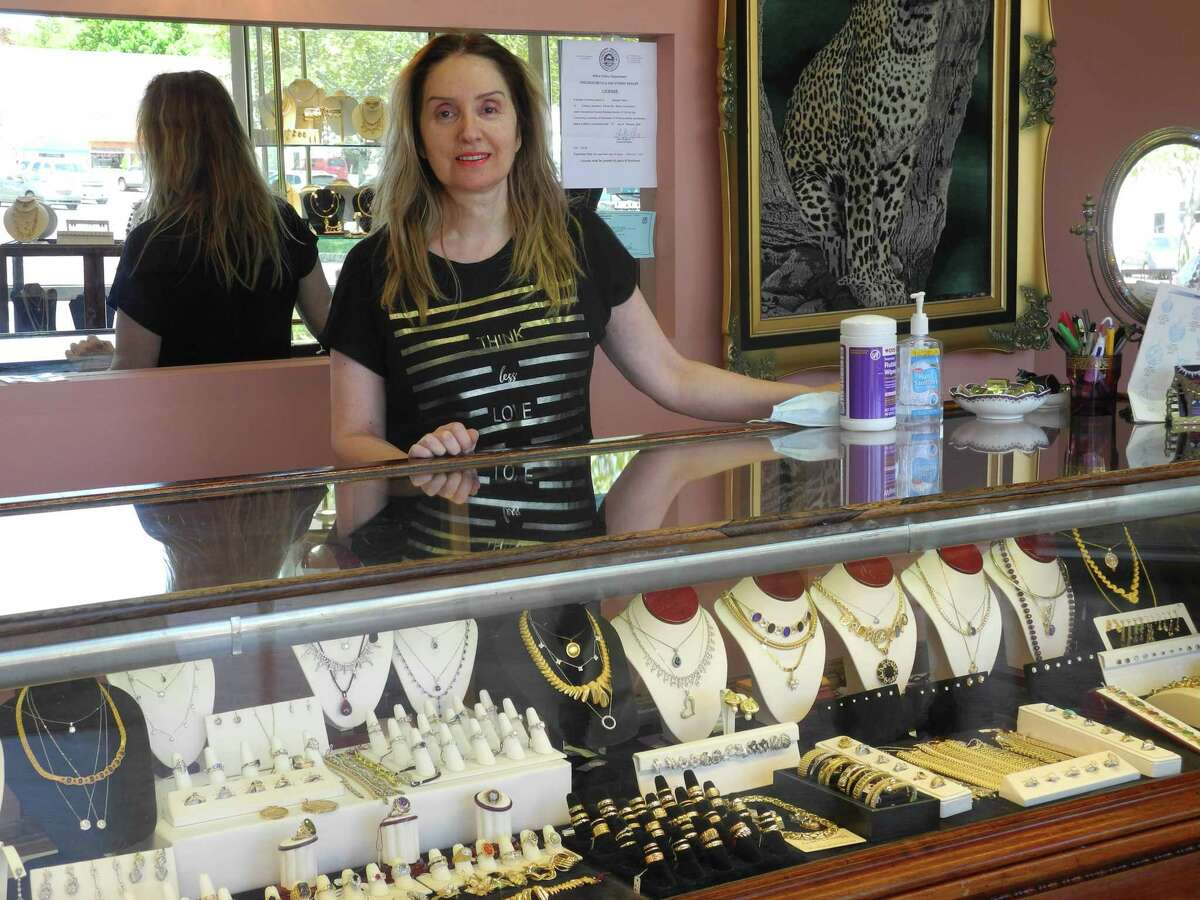 Sonya Taheri, owner of Campus Jewelers in Wilton Center, took off her mask for a photo as the shop reopened on May 20.