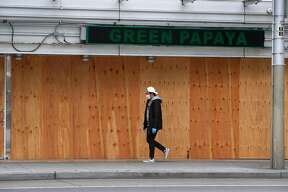 Plywood boards cover the windows at Green Papaya restaurant at the Fifth and Mission garage in San Francisco, Calif. on Wednesday, May 20, 2020. Shuttered since shelter-in-place restrictions went into place, the Vietnamese restaurant depends heavily on walk-in business from convention attendees so its future is unknown because it's unclear when gatherings at Moscone Center will resume.