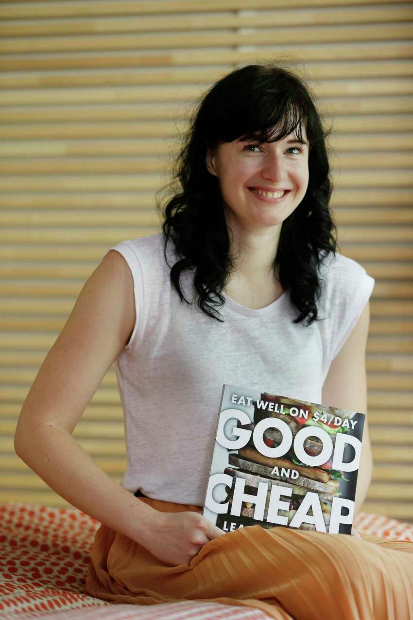 In this July 8, 2014 photo, Leanne Brown poses for a picture with her new cookbook a€œGood and Cheap,a€ in her apartment in New York. The book is aimed at helping put good, inexpensive food on the table without spending hours over it. The book, originally written for a mastera€™s thesis was a surprise hit online, prompting Brown to turn to a Kickstarter fundraising campaign to put hardcover copies in the hands of the people who need it most. (AP Photo/Seth Wenig) ORG XMIT: NYSW111