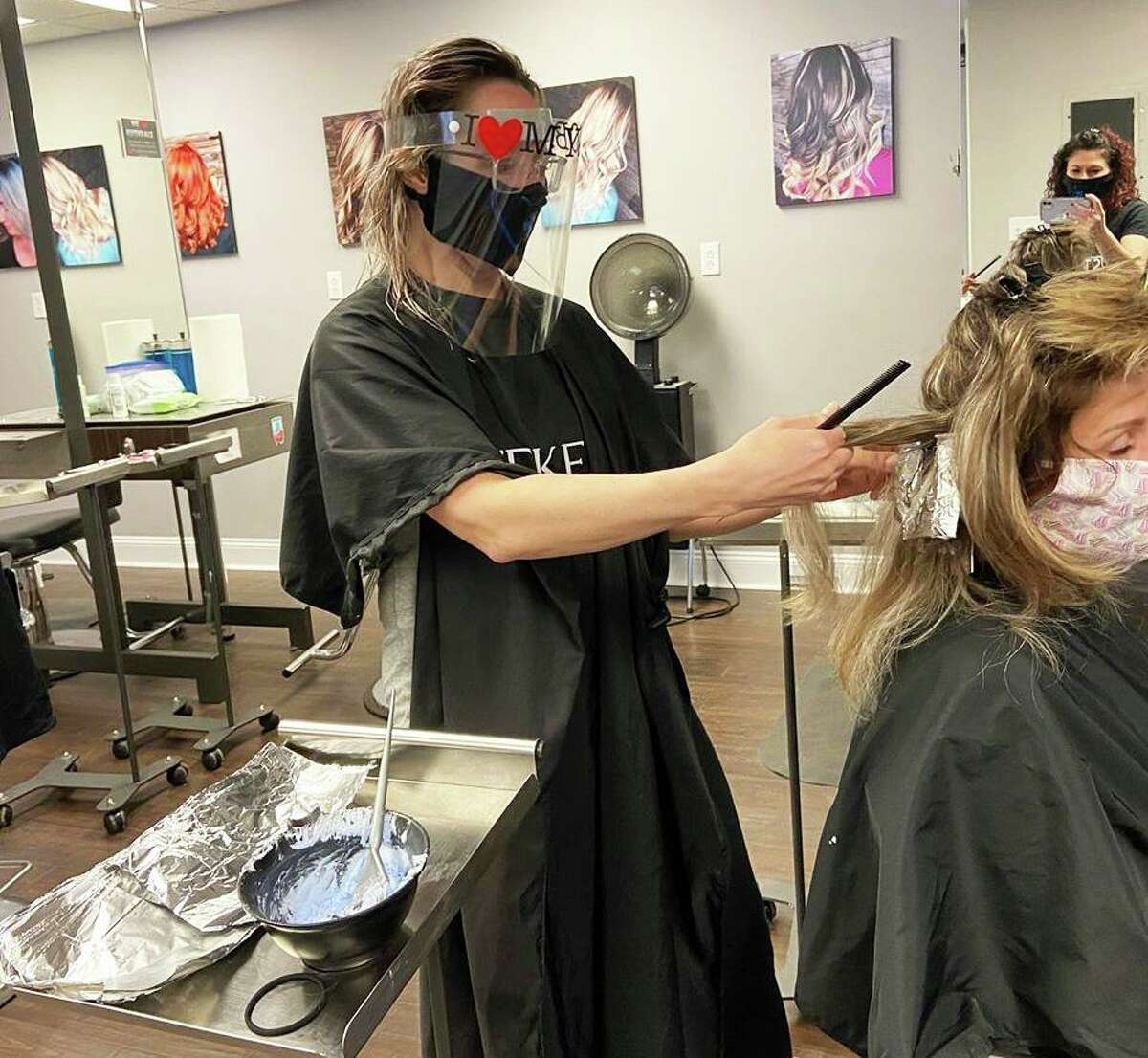 Kim Kelly, a stylist at Jessica's Color Room in Middletown, practices the new coronavirus safety measures on a coworker in preparation for the opening of barber shops and beauty salons during the pandemic. Two days before the scheduled reopening, the governor pushed it off to June 1.