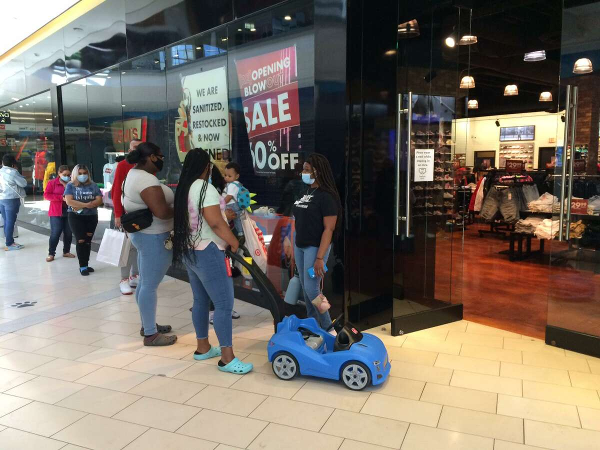 Customers wait outside the Eblens clothing store in Westfield Trumbull Mall on May 20.