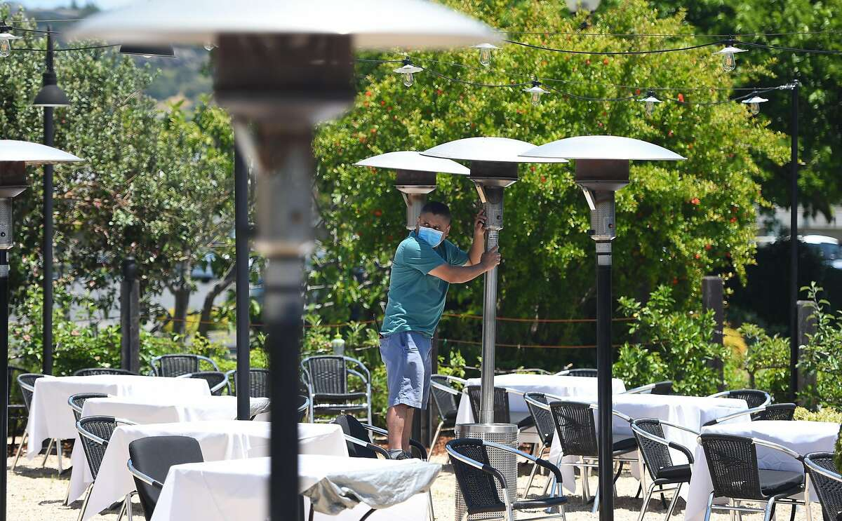 Employee Carlos Olvera sets up outdoor heaters as workers prepare Cole's Chop House for on-site dining in Napa, California on May 20, 2020. Taking advantage of Napa's liberalized shelter-in-place rules, Cole's is reopening its dining room for customers with new safety requirements in place.