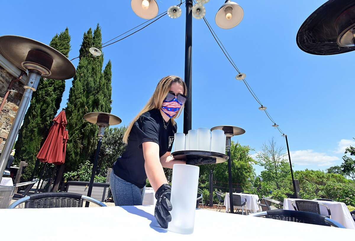 Employee Bryce Gagne sets up candles as workers prepare Cole's Chop House for on-site dining in Napa, California on May 20, 2020. Taking advantage of Napa's liberalized shelter-in-place rules, Cole's is reopening its dining room for customers with new safety requirements in place.