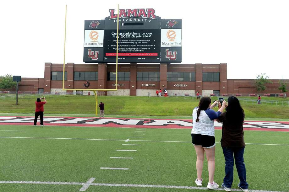Graduates and families spread out to watch as Lamar University Spring 2020 graduates's names and photos by college are displayed on the jumbo screen at Provost Umphrey Stadium as the Lamar school song plays during a virtual commencement ceremony Friday. Graduates and their families were invited to take photos as their name and picture was displayed, although early morning rains made for a sparse attendance at the event start. Photo taken Friday, May 15, 2020 Kim Brent/The Enterprise Photo: Kim Brent / The Enterprise / BEN