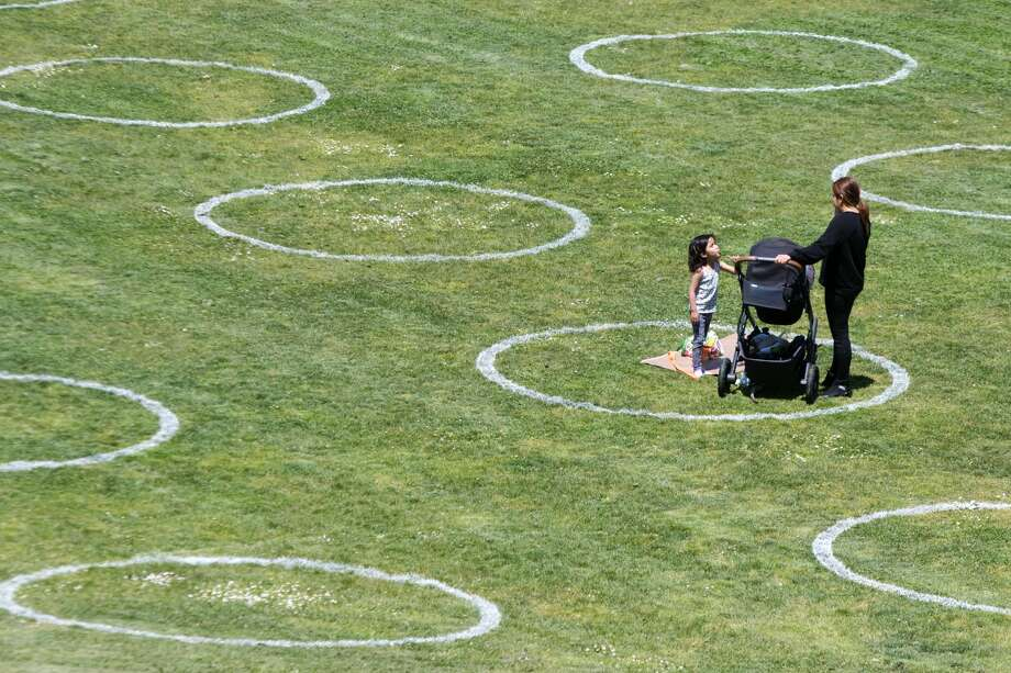 Social Distancing chalk circles are visible in a grass field at Mission Dolores Park in San Francisco on May 20, 2020. The circles mark the required safe social distancing space required during the COVID-19 coronavirus and were created by the San Francisco Rec and Parks Dept. Photo: Douglas Zimmerman/SFGate / SFGate