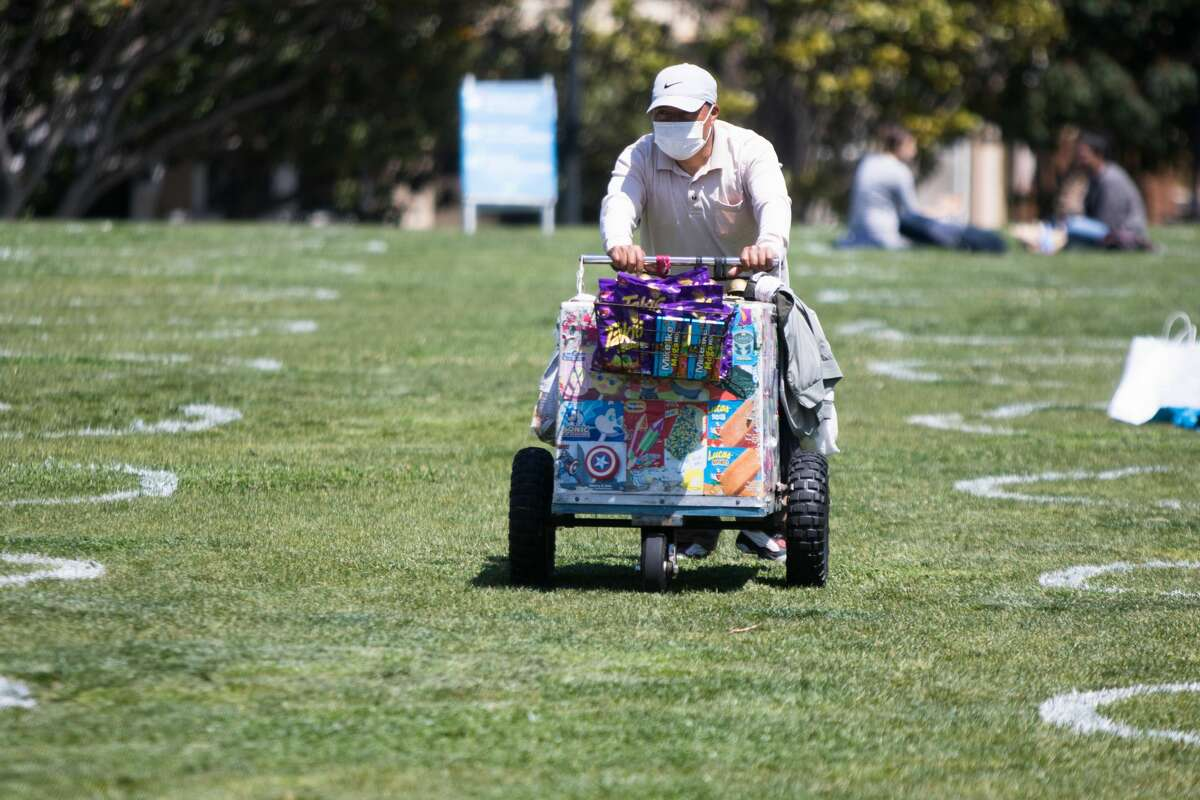 FILE - An ice cream vendor walks through social distancing chalk circles visible in a grass field at Mission Dolores Park in San Francisco on May 20, 2020.