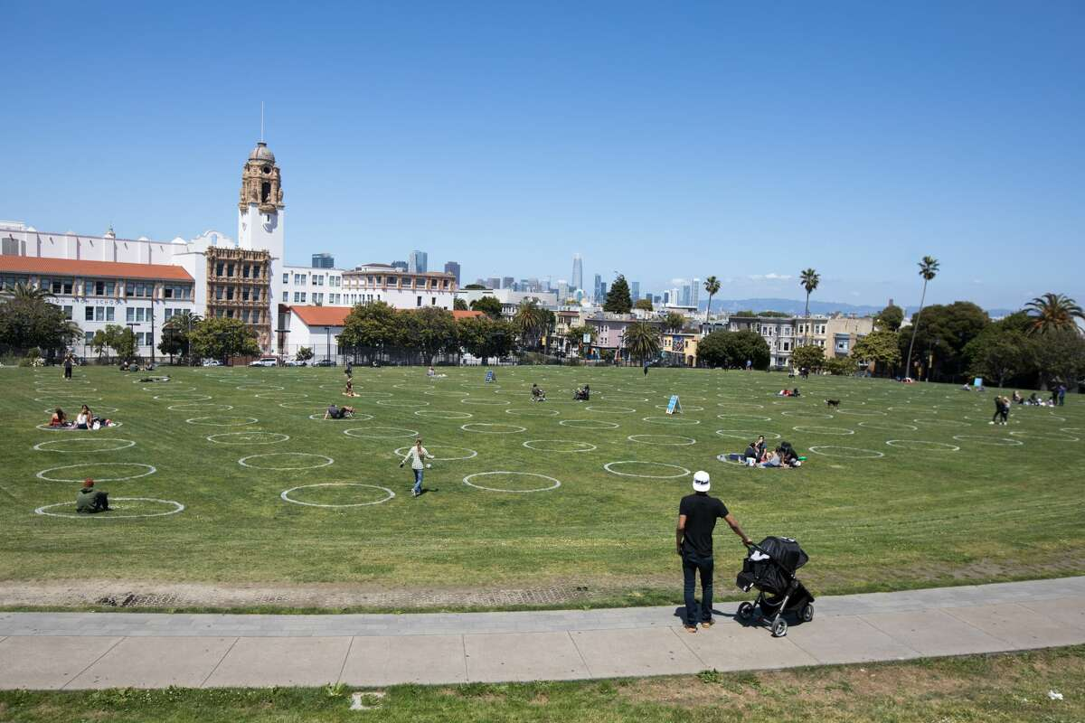 FILE: Social-distancing chalk circles are visible in a grass field at Mission Dolores Park in San Francisco on May 20, 2020.