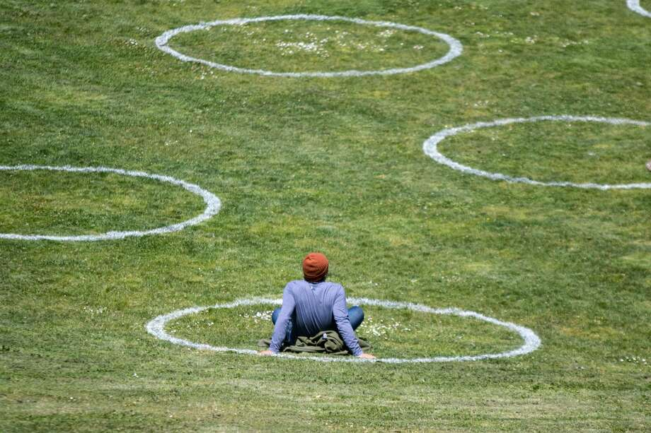 A man rests inside a social distancing chalk circles in a grass field at Mission Dolores Park in San Francisco on May 20, 2020. The circles mark the required safe social distancing space required during the COVID-19 coronavirus and were created by the San Francisco Rec and Parks Dept. Photo: Douglas Zimmerman/SFGate / SFGate