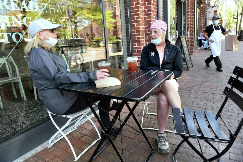 Susan Rerat, left, of New Haven sits with Mary Sykes of New York City at the outdoor seating for Maison Mathis on Elm Street in New Haven on the first day of the phased reopening of businesses in Connecticut on May 20, 2020.