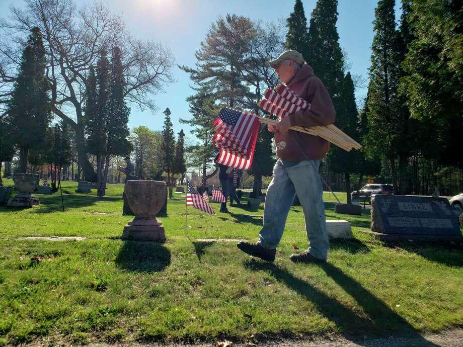 Tom Gorney searches for veteran's graves to place flags at with other Catholic War Veterans Duchon Post volunteers at Mount Carmel Cemetery Wednesday morning. (Arielle Breen/News Advocate)