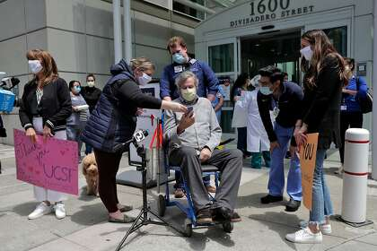 Ronald Jay Temko does a live video feed surrounded by family, friends and medical personnel as he is discharged from UCSF Mount Zion Hospital, after being hospitalized for over 61 days with COVID-19 in San Francisco. Calif., on Wednesday, May 20, 2020. Temko was in a coma for 21 days, on a ventilator for 34 days, and had a feeding tube for 40 days. Despite all the odds, he is now up and walking, as mentally sharp as ever, and beyond grateful to be alive. He will now get to walk his daughter down the aisle, hold his new baby granddaughter, and teach his grandson how to play golf.