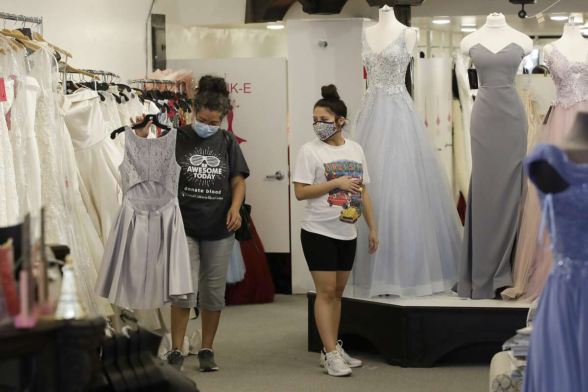 Salesperson Valerie Serrato, right, shows a dress to a customer at Pink E Boutique Wednesday, May 20, 2020, in Visalia, Calif. Tulare County's board of supervisors voted 3-2 Tuesday to move further into the state's four-stage reopening plan than is allowed. That means nearly all businesses and churches could reopen, though county officials said businesses should adhere to state guidelines on social distancing and other health measures. (AP Photo/Marcio Jose Sanchez)