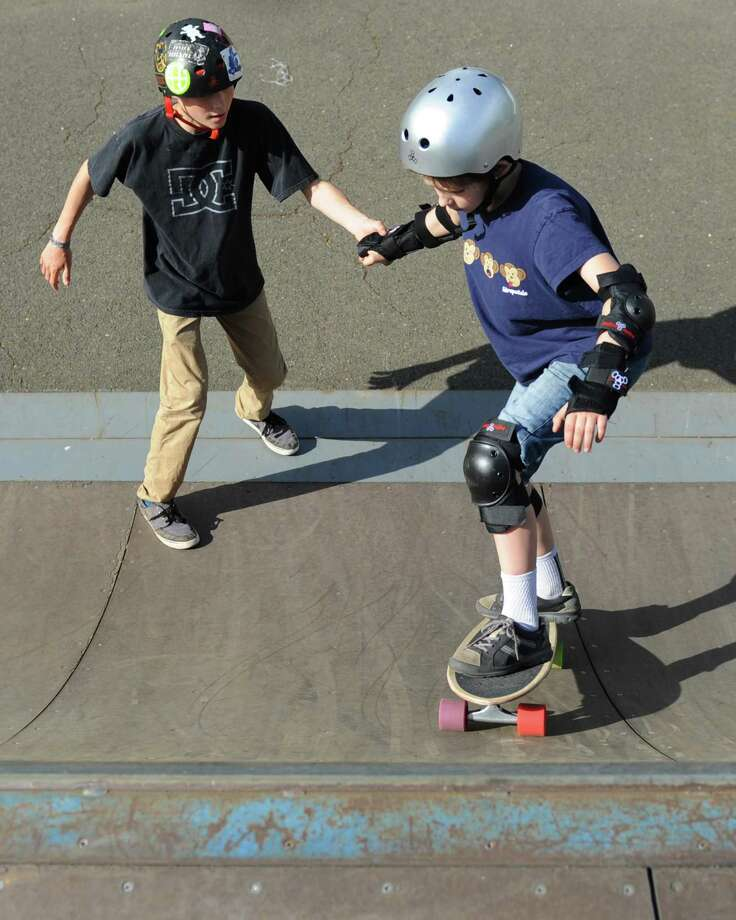 The Greenwich Skate Park, seen here in 2015 as Cos Cob resident Martin Curley, 14, helps out Charlie McLeod, 10, enjoy it, will reopen this weekend on a limited basis including with hard caps on the number of skaters who can use it at once. Photo: Tyler Sizemore / Tyler Sizemore / Greenwich Time