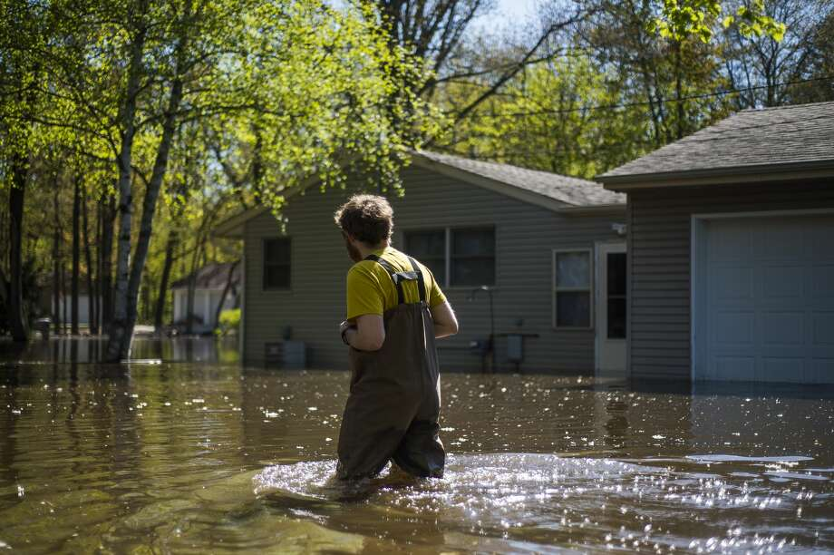 Nick Fox wades through floodwater to reach his home on Nurmi Drive Wednesday afternoon, May 20, 2020. (Katy Kildee/kkildee@mdn.net) Photo: (Katy Kildee/kkildee@mdn.net)