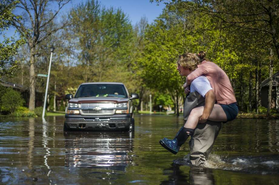 Ryan Stadelmaier, 16, gifts a piggyback ride to his sister, Rachel Stadelmaier, 27, as they cross Walden Woods Drive while helping residents tend to their flooded homes Wednesday, May 20, 2020. (Katy Kildee/kkildee@mdn.net) Photo: (Katy Kildee/kkildee@mdn.net)