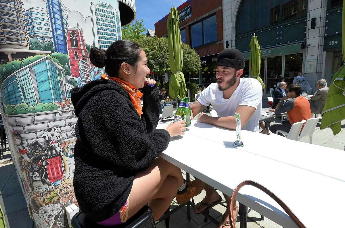 Anna Astudillo and friend Chris Rodriguez, both of Stamford, enjoy drinks and a meal at Capriccio Cafe in Stamford on Wednesday. The two were among the first customers to enjoy outdoor dining on Bedford Street, as businesses in the downtown area begin to reopen following a local and state wide shutdown to patrons dining in response to the COVID-19 Pandemic.