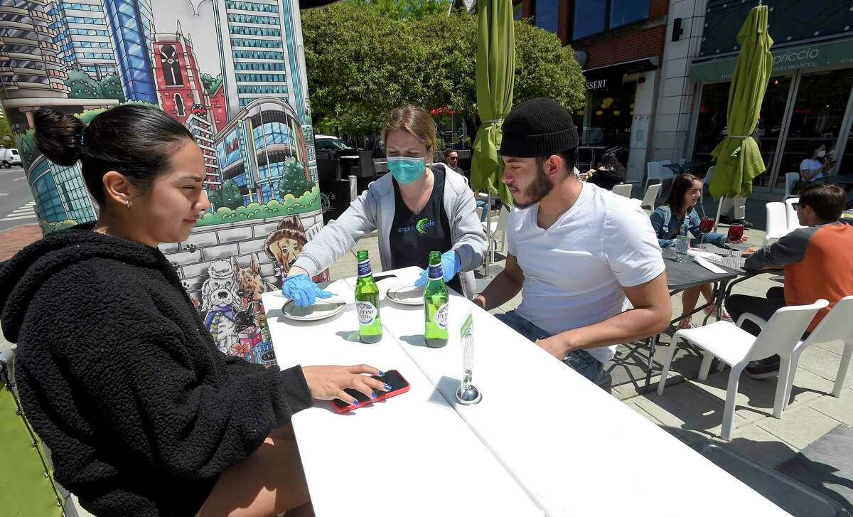 Server Mimi Carzaster brings out a table set up for Ana Astudillo and friend Chris Rodriguez, both of Stamford, to use as they enjoy drinks and a meal at Capriccio Cafe in Stamford, Connecticut on May 20, 2020. The two were among the first customers to enjoy outdoor dining on Bedford Street, as businesses in the downtown area begin to reopen following a local and state wide shutdown to patrons dining in response to the COVID-19 Pandemic.