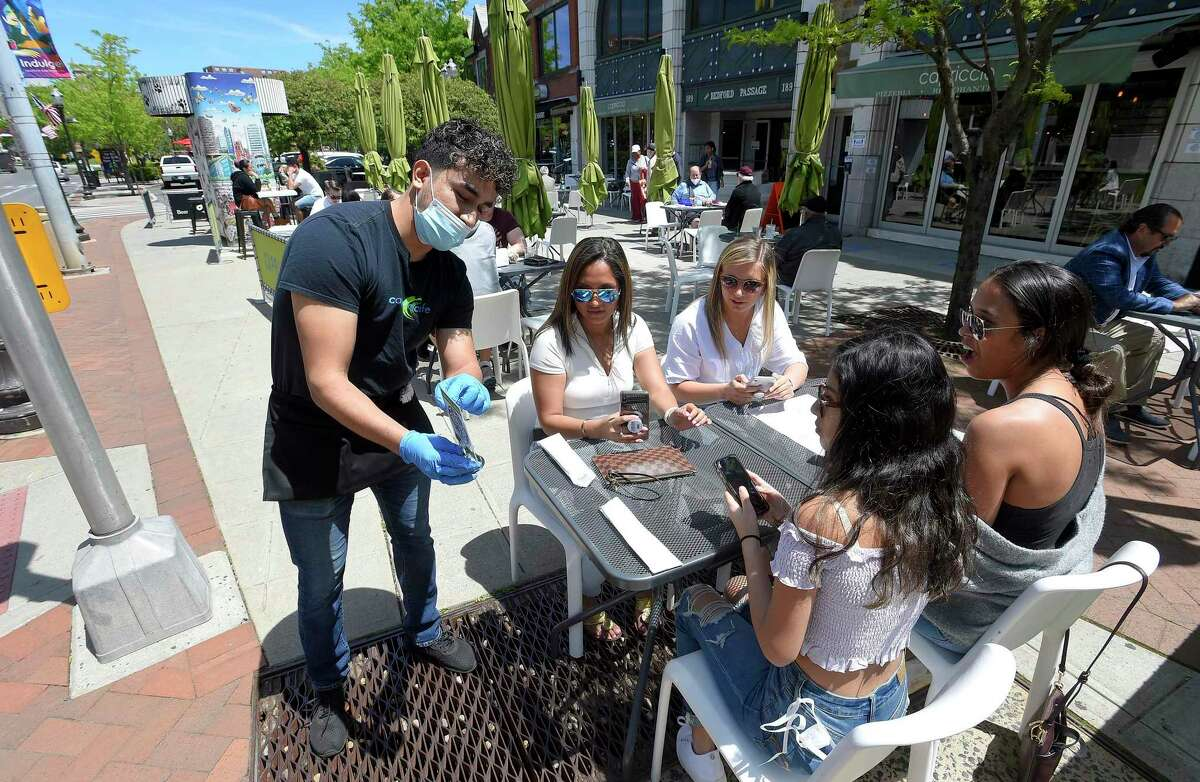Server Enzo Caso helps patrons set up a Virtual Menu APP on there phone as they prepare to place an order at Capriccio Cafe in Stamford, Connecticut on May 20, 2020.