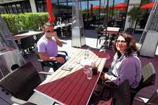 Stavros Begetis of Stamford and his mother, Connie Begetis, prepare to enjoy a meal at Tomato Tomato in Stamford on Wednesday. The two were among the first customers to enjoy the return of outdoor dining, as businesses in the area begin to reopen following a statewide shutdown to patrons dining in response to the COVID-19 Pandemic.