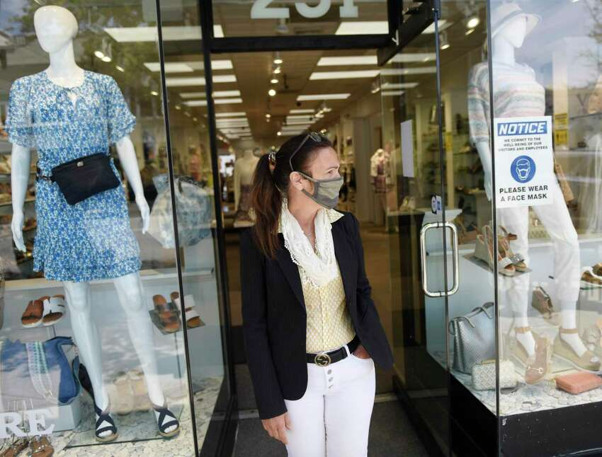 Store manager Ann Marie Spallone wears a mask while welcoming shoppers to Shoes 'N' More in Greenwich, Conn. Wednesday, May 20, 2020. Nonessential retail stores and restaurants were allowed to open Wednesday, following strict precautions set forth by Gov. Lamont.