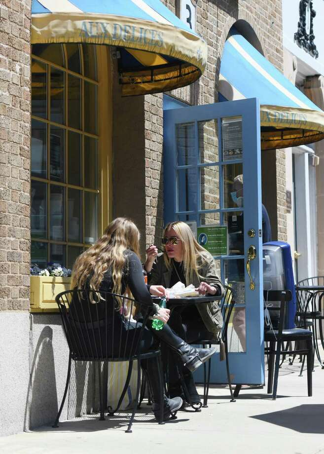 New York City residents Elle Berman, left, and Ellen Cole dine outside at Aux Delices in Greenwich, Conn. Wednesday, May 20, 2020. Photo: File / Tyler Sizemore / Hearst Connecticut Media / Greenwich Time