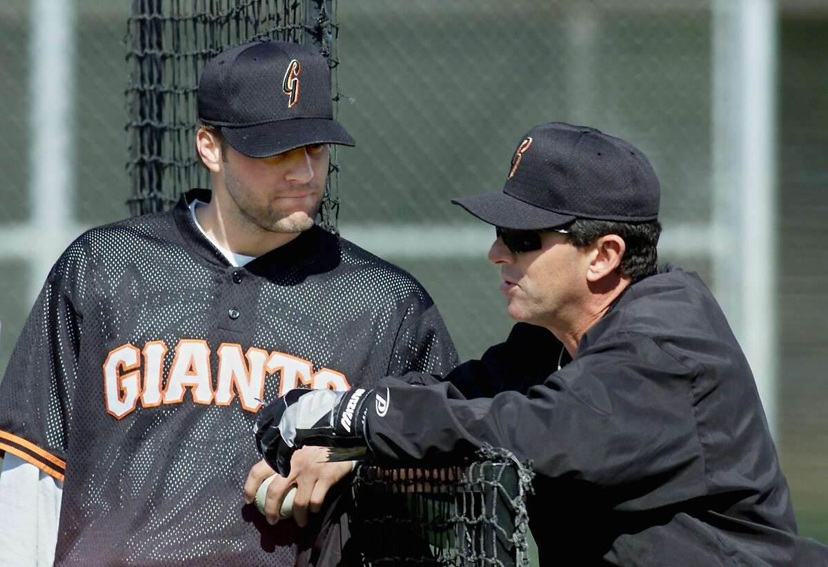 One of the many jobs Carlos Alfonso has held for the Giants is pitching coach. Here he offers advice to Shawn Estes during the team's 2000 spring training in Scottsdale, Ariz.