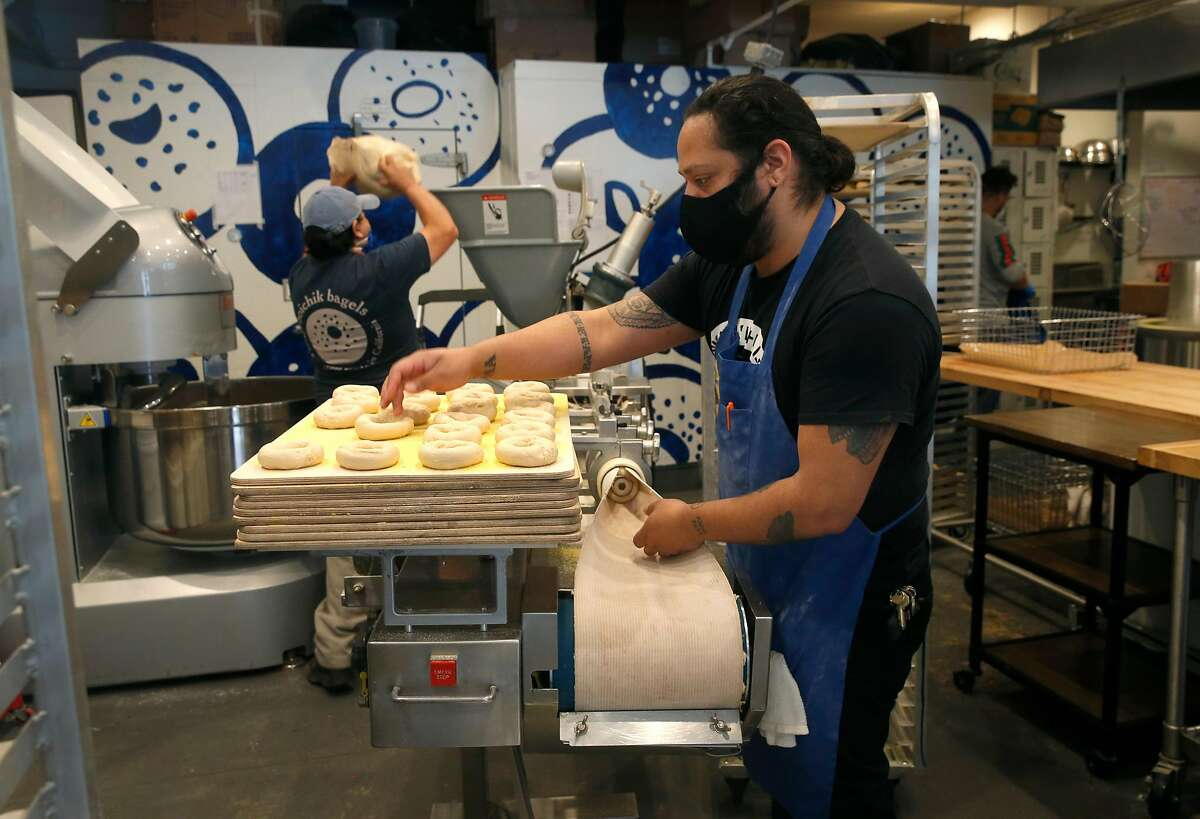 Dan Duran places bagels on a tray as Armando Carapia adds dough to a machine (background) at Boichik Bagels in Berkeley, Calif. on Wednesday, May 20, 2020. Business has remained strong at Boichik and other local bakeries during the coronavirus pandemic.
