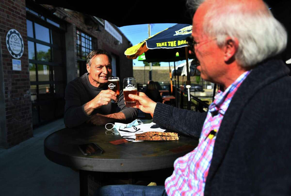 Fred Daniele, left, of Milford, and his friend Jim enjoy a beer during the reopening of the outdoor dining area at Brewport in Bridgeport, Conn. on Tuesday, May 19, 2020.