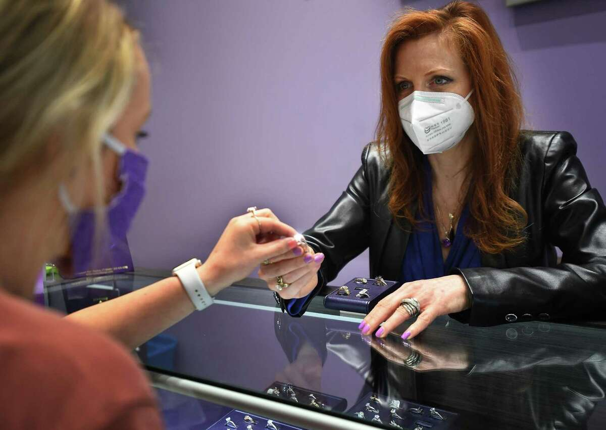 Kathleen McNichols-Marks, right, owner of Marks of Design, meets with customers by appointment during re-opening day at the jeweler in Shelton, Conn. on Tuesday, May 19, 2020.