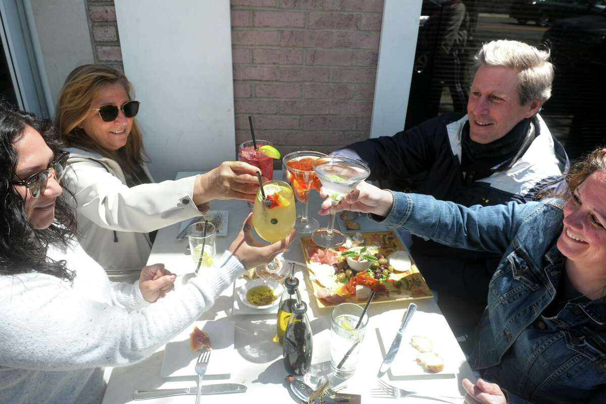From left, co-workers Denna Rosario, Linda Forrante, Steve Dzyck and Danelle Brown raise their drinks in a toast while they enjoy lunch on the sidewalk tables in front of Pizzeria Molto, in Fairfield, Conn. May 20, 2020.