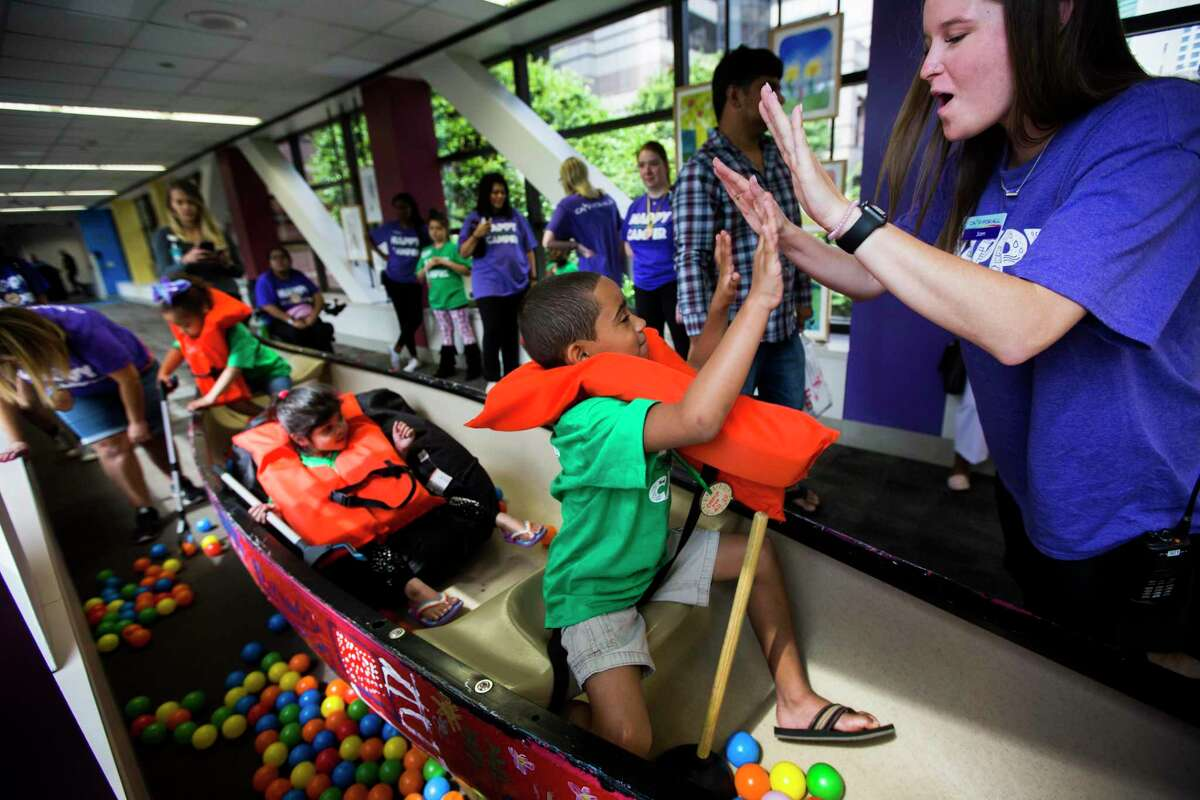 Jaiden, 7, high-fives a staff member of the Camp for All during simulated fishing trip at the hallway of the Texas Children's Hospital on Tuesday, June 11, 2019, in Houston.