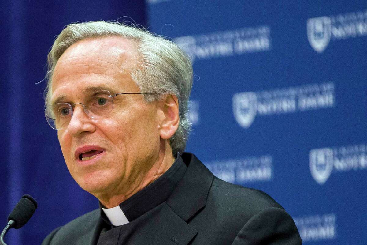 FILE - In this Oct. 11, 2019, file photo, University of Notre Dame President Rev. John I. Jenkins speaks during a press conference in South Bend, Ind. The presidents of the University of Miami and Notre Dame say in separate interviews that they expect the football season to be played, though both raised the very real possibility of crowds being much smaller than usual or eliminated entirely. (Robert Franklin/South Bend Tribune via AP, File)