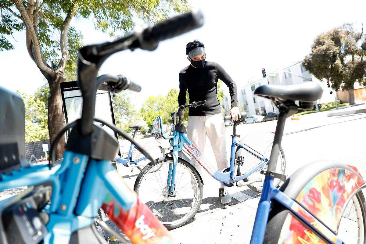 Jalinn Ahmad readies to ride a Lyft bike to his sister's apartment in San Francisco, Calif., on Tuesday, May 19, 2020. Ahmad is a laid off tech worker has been filling his time studying for his CIMA certification.