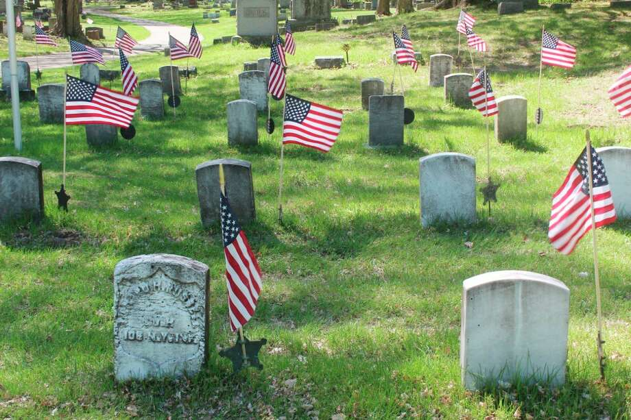 Local boy scouts and veterans visited to Highlandview Cemetery on Wednesday to place American flags on veterans' tombstones in preparation of Memorial Day on Monday. While many Memorial Day celebrations have been canceled, The American Legion Post No. 98 will have a brief ceremony at Holland Park Monday as well. (Pioneer photo/Catherine Sweeney)