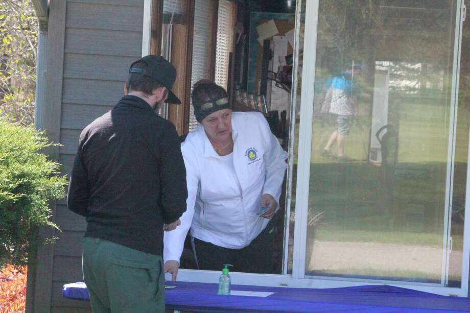 Chris Balulis waits on a customer at Marquette Trails Golf Course near Baldwin last week. Since golfers aren't allowed in the clubhouse, she was checking them in through a building window. (Star photo/John Raffel)