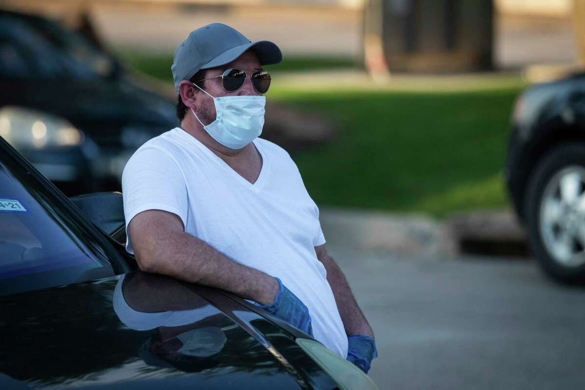 Abel Cervantes, who says he tested positive for the coronavirus and has had to continue to work at Quality Sausage Co. in Dallas, listens to Carlos Quintanilla talk about a lawsuit against the company Tuesday, May 19, 2020. (Yffy Yossifor/Star-Telegram via AP)