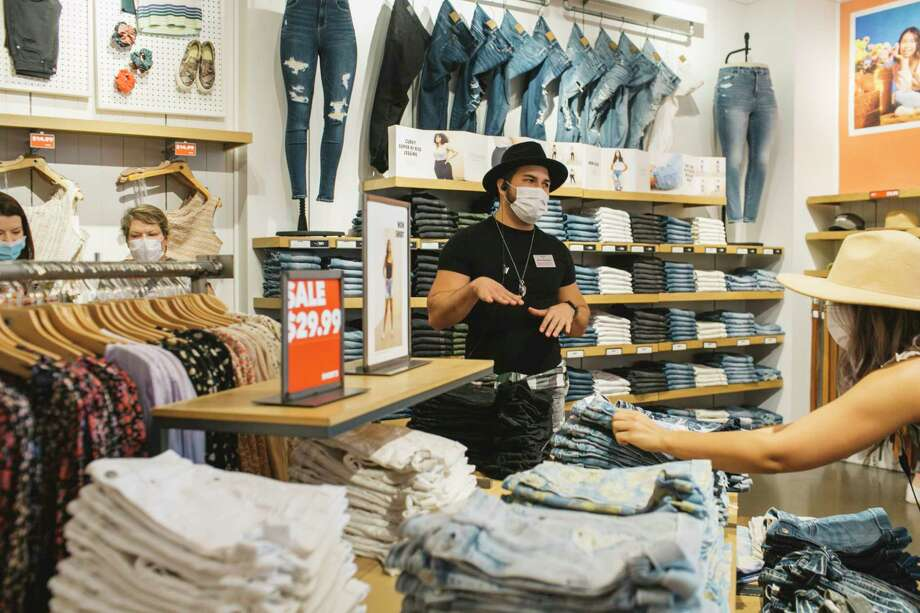 Matthew Mitchell talks with customers as Sierra Phillips adjusts a display at American Eagle Outfitters at Easton Town Center in Columbus, Ohio, on May 15, 2020. Photo: Photo For The Washington Post By Andrew Spear. / Andrew Spear