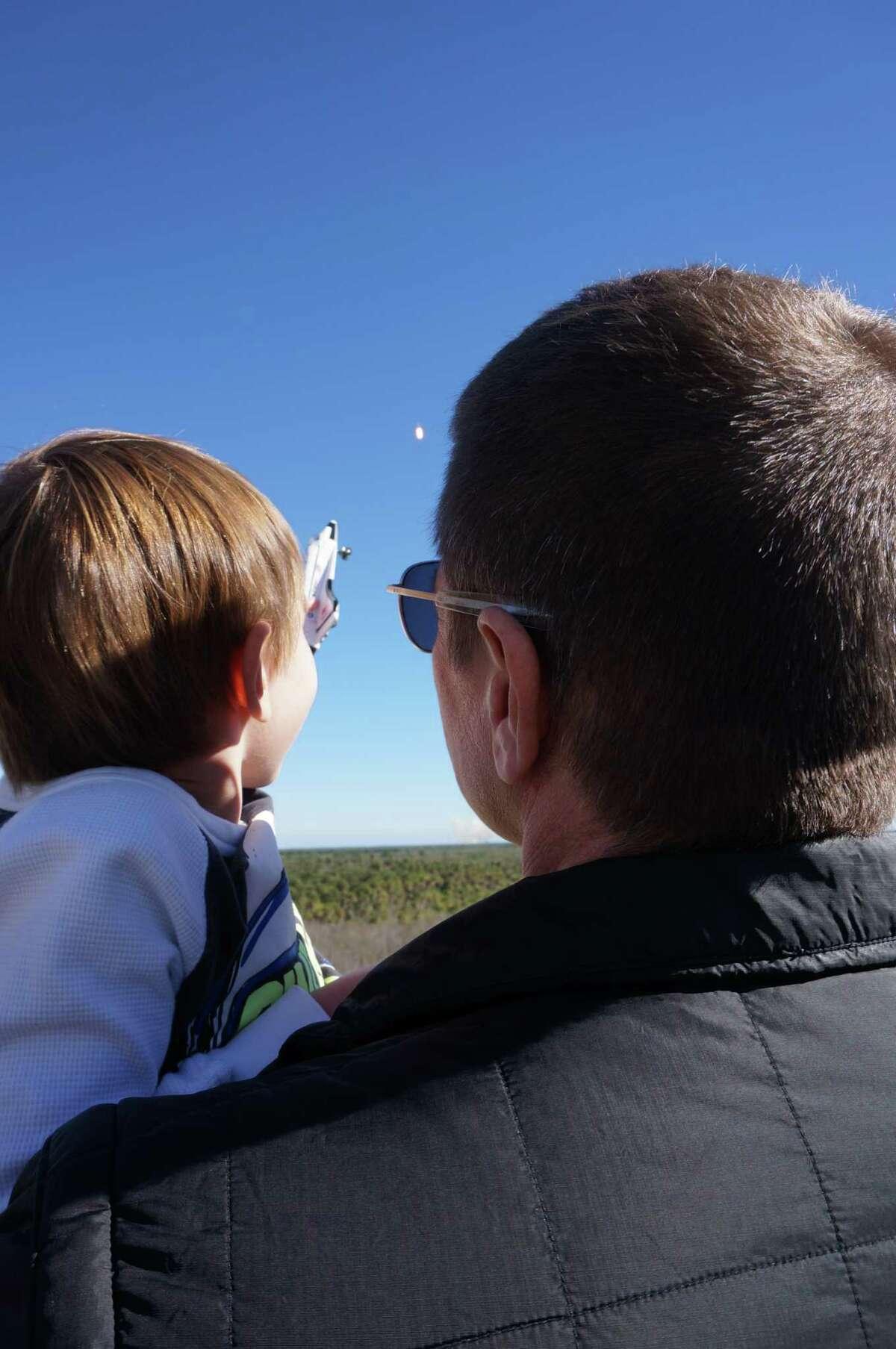 Astronaut Bob Behnken and his sonTheodore watch a SpaceX rocket launch in December 2018.
