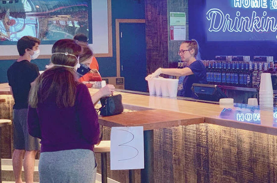 A Champaign bar sells drinks to-go this week. Bars and restaurants are among the next group of businesses that will have some restrictions eased May 29, but they will be required to use outdoor seating and follow social-distancing guidelines. Photo: Patrick Gorski | NurPhoto (Getty Images)
