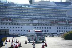 An ambulance drives away from the Diamond Princess cruise ship, operated by Carnival Corp., in Yokohama, Japan, on Feb. 12, 2020.