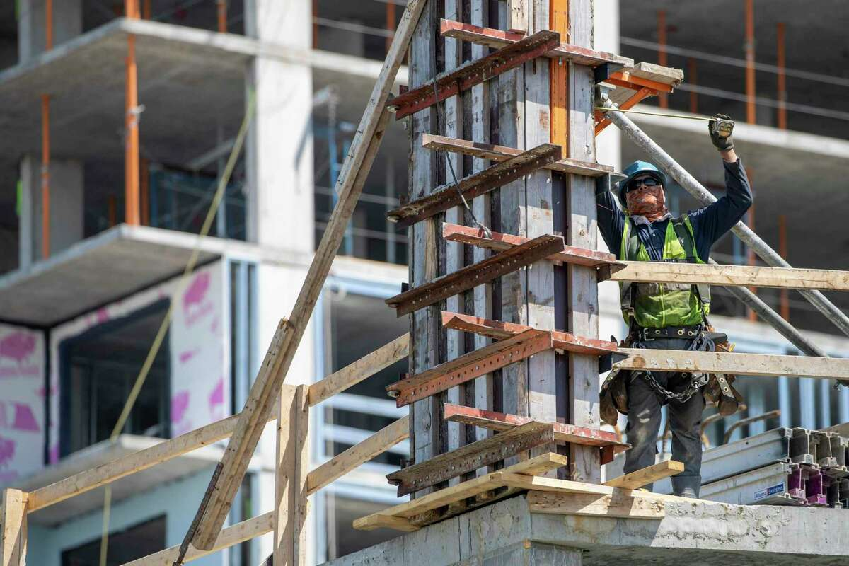A construction worker takes a measurement while working at a residential building construction site at the Harbor Point redevelopment site, Wednesday, May 20, 2020, on the Stamford, Conn., waterfront. (AP Photo/Mary Altaffer)
