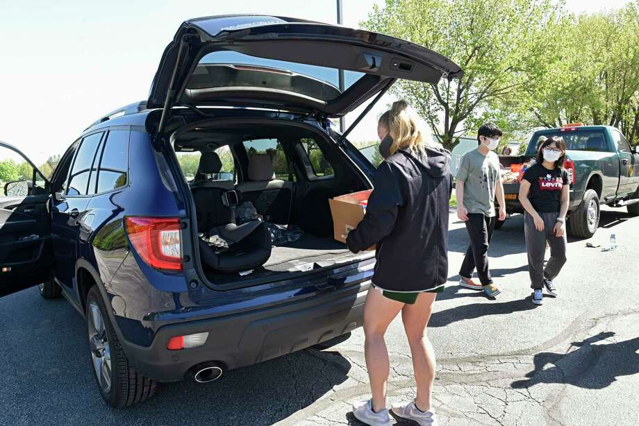 Volunteers in Clifton Park, N.Y., collect donations from the trunk of a vehicle during a drive-up, drop-off food drive May 20, 2020. Photo: Lori Van Buren / Albany Times Union / 40049325A