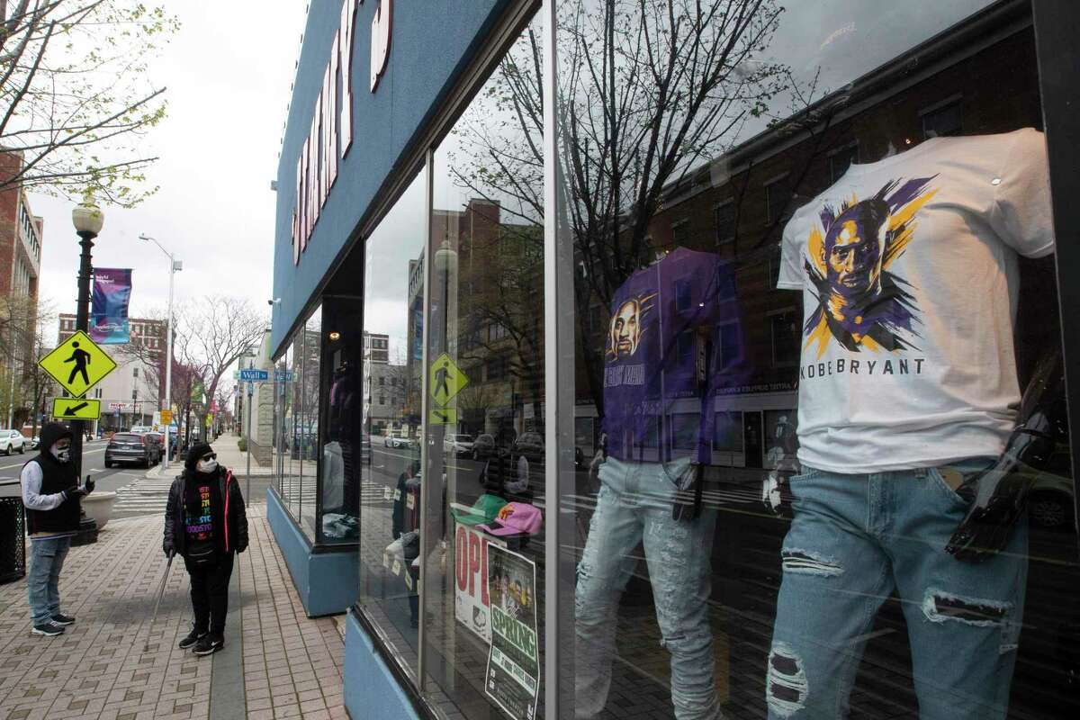 In this April 27, 2020 file photo, a couple of passersby wearing face masks walk past a closed clothing store on Main Street in downtown in Bridgeport, Conn. Connecticut lost jobs in April.