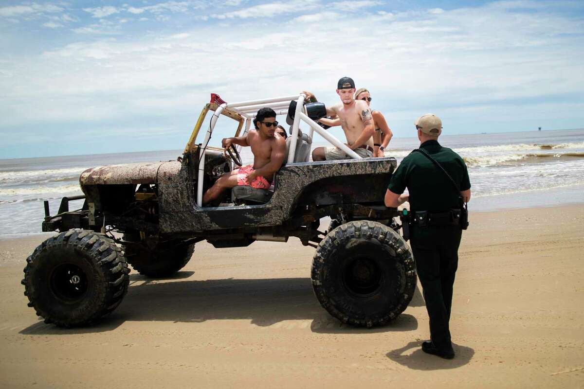 In this Sunday, May 17, 2020 photo, a group of people riding in a Jeep during the Go Topless Jeep Weekend get stopped by a Galveston County Sheriff's Office deputy at Crystal Beach in the Bolivar Peninsula, Texas. (Marie D. De Jesús/Houston Chronicle via AP)
